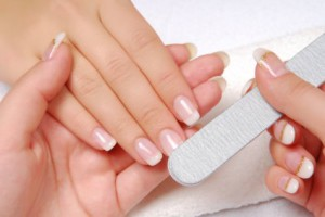 Studio nail beautician polishing female nails